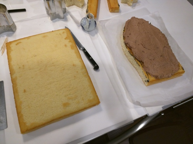 Step 4: Use food coloring markers to draw the shape of the cake, then cut it with knife. Frost one side of the cutout shape.